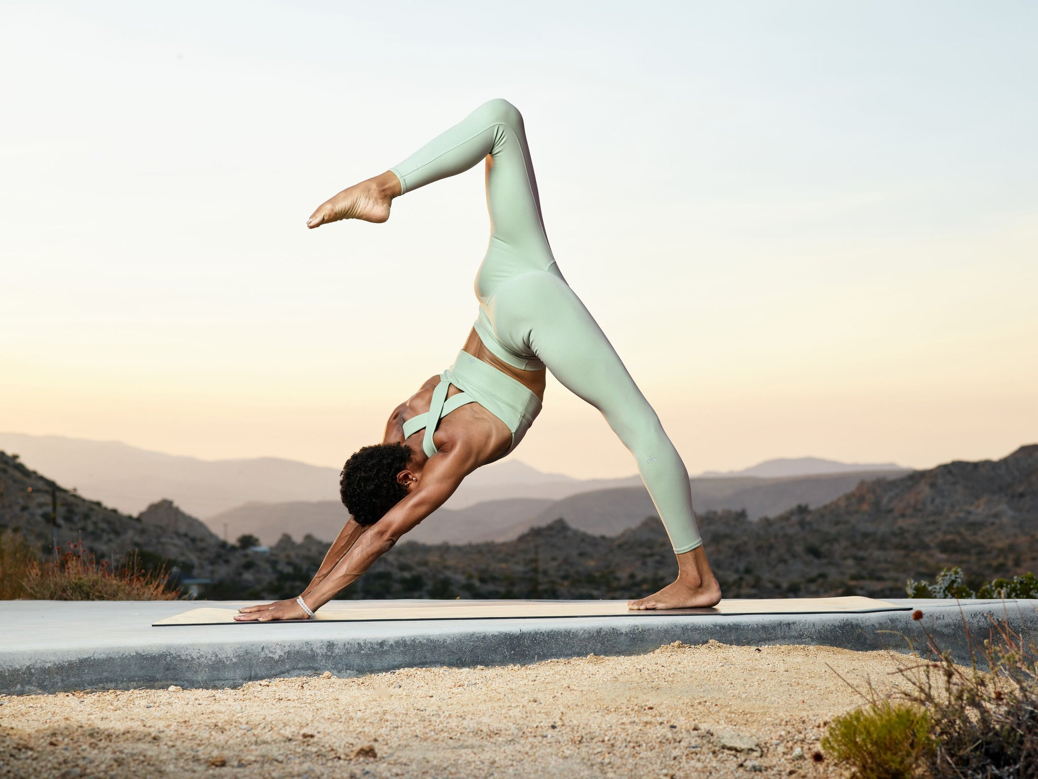 A woman performing a Three-Legged Downward Dog in front of a sunset wearing a workout set with matching pastel green yoga leggings and cross-back sports bra.