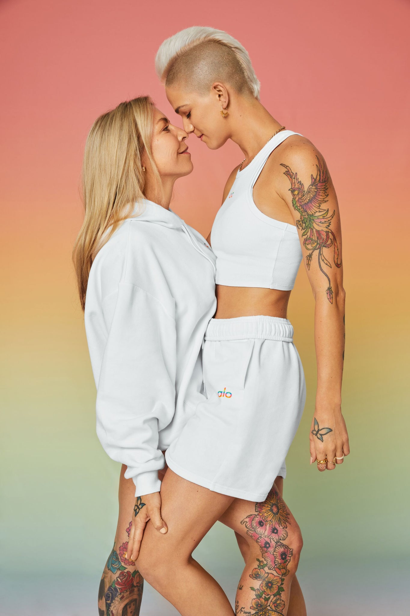 Two women posing in front of an ombre rainbow backdrop wearing all white clothing with rainbow logos.