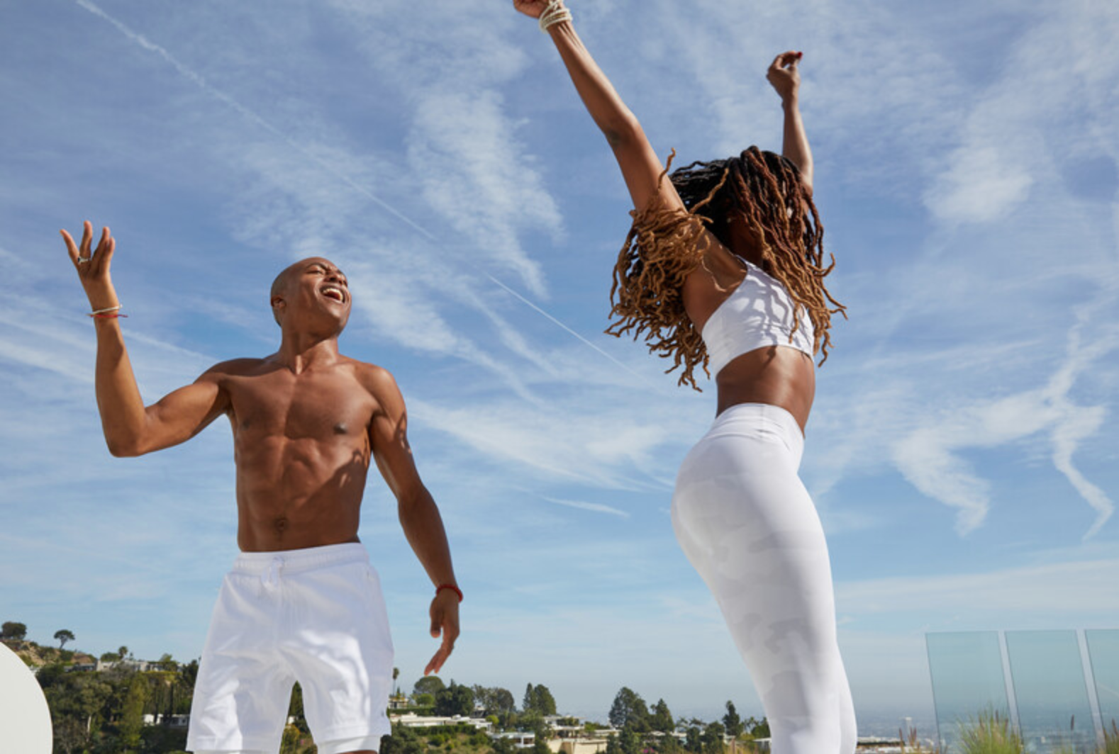 A man and woman wearing all white Alo clothing dancing to music in celebration.