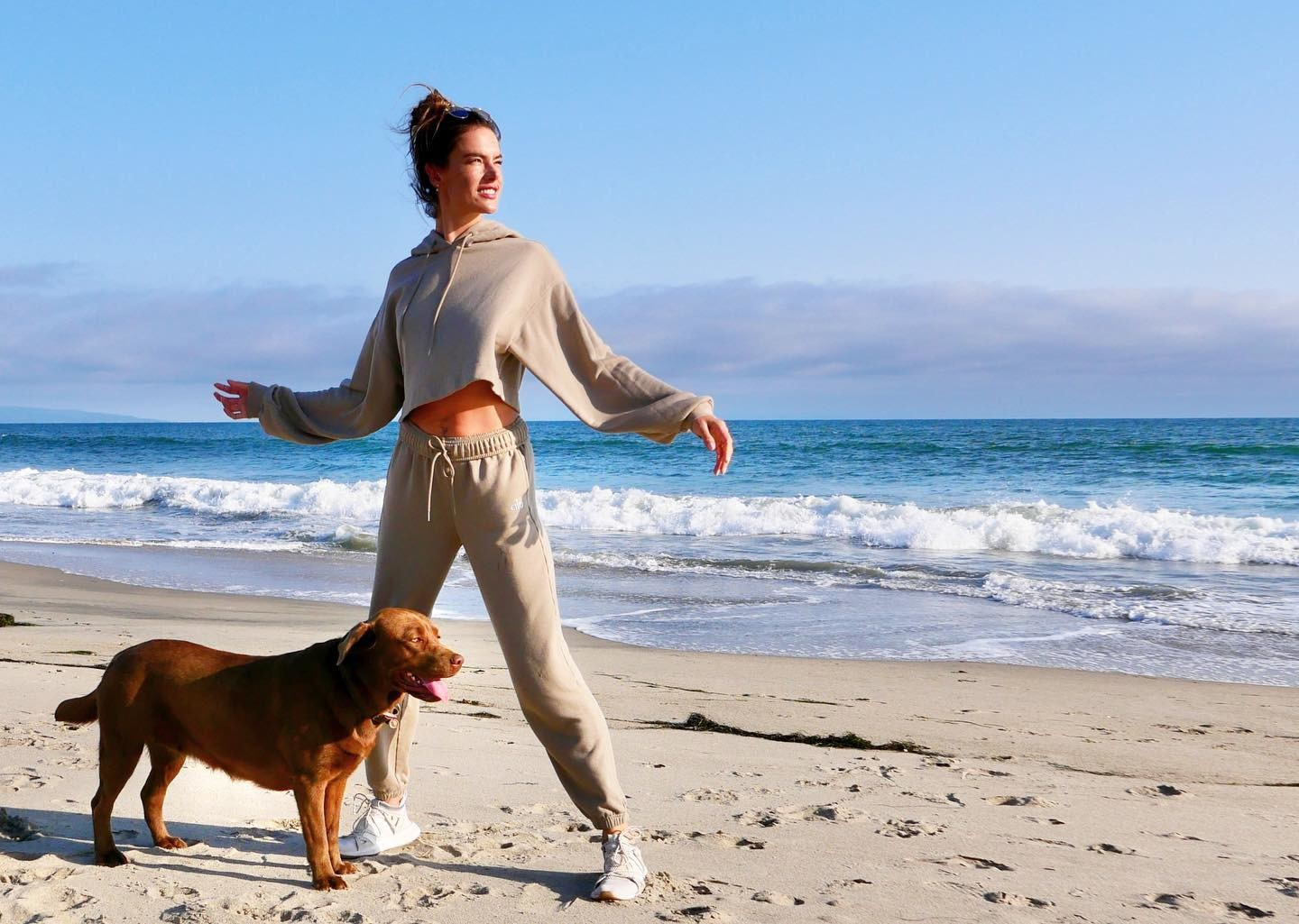 @alessandraambrosio wearing the Bae Hoodie and Accolade Sweatpants while throwing a ball for her dog at the beach.