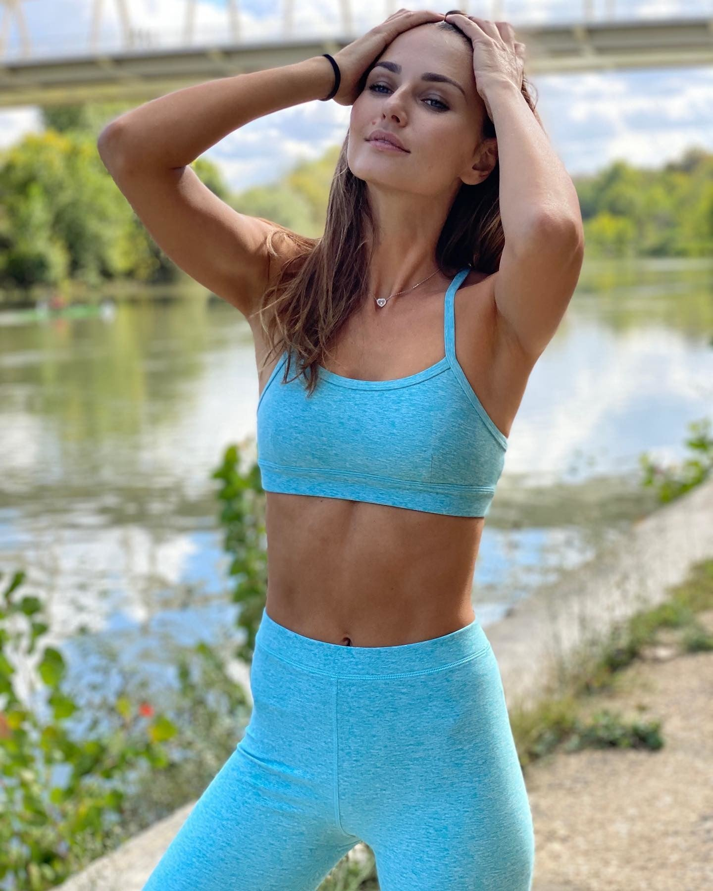 @annasafroncik wearing a matching turquoise sports bra with high-waisted yoga pants while walking alongside the river.