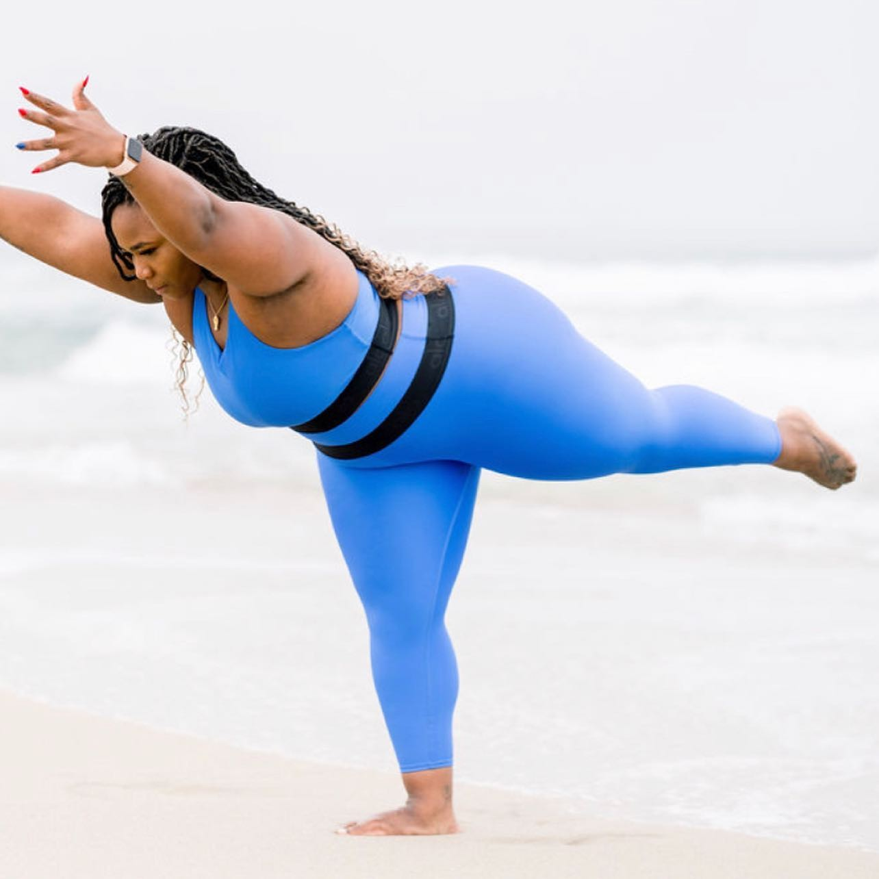 @christajanine wearing bright blue capri leggings with a matching sports bra top while performing Warrior III on the beach.
