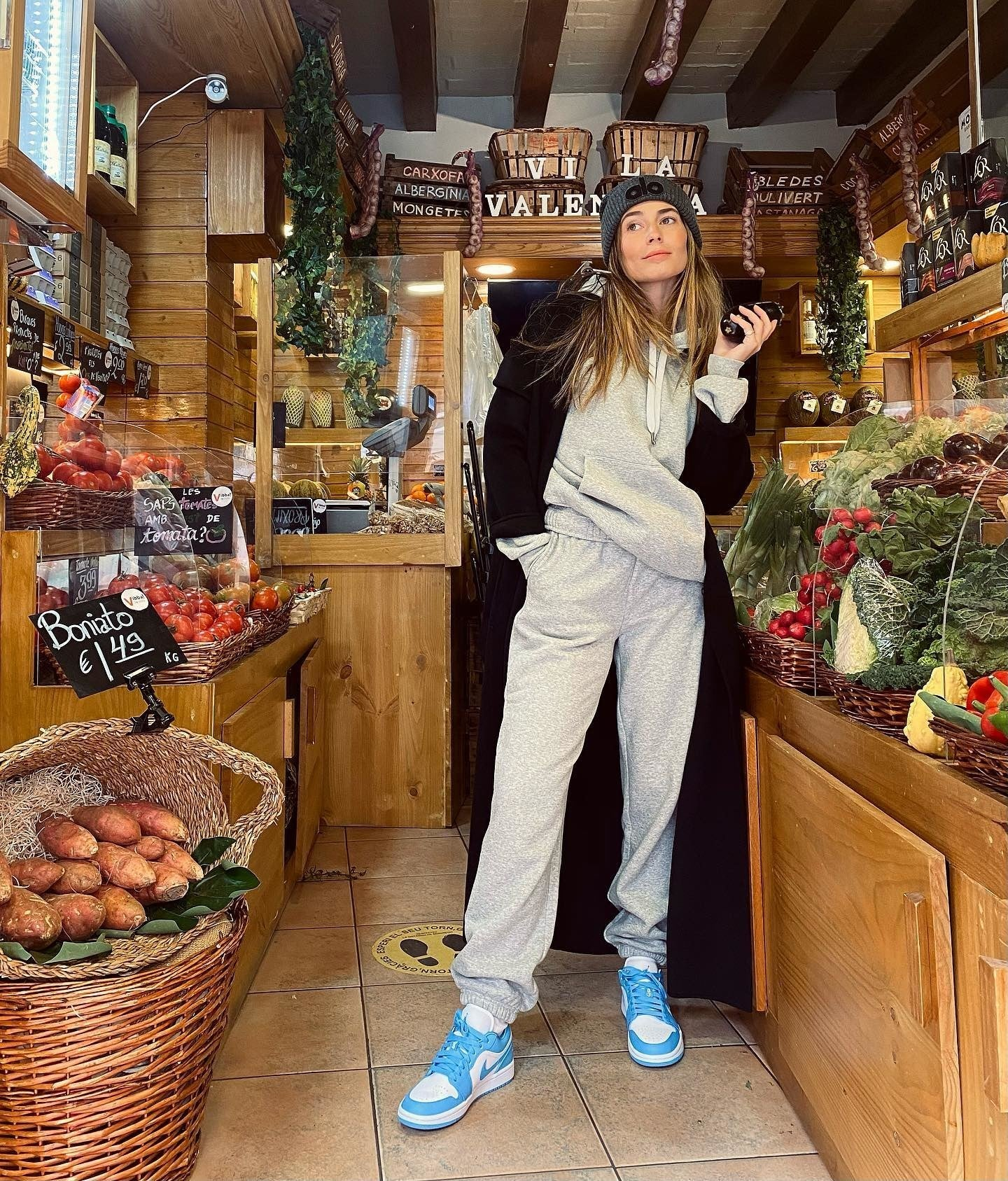 @coralsimanovich wearing the Accolade Hoodie and Accolade Sweatpants with an oversized black trench coat, Alo beanie, and turquoise blue sneakers for a street look while visiting the farmers' market.