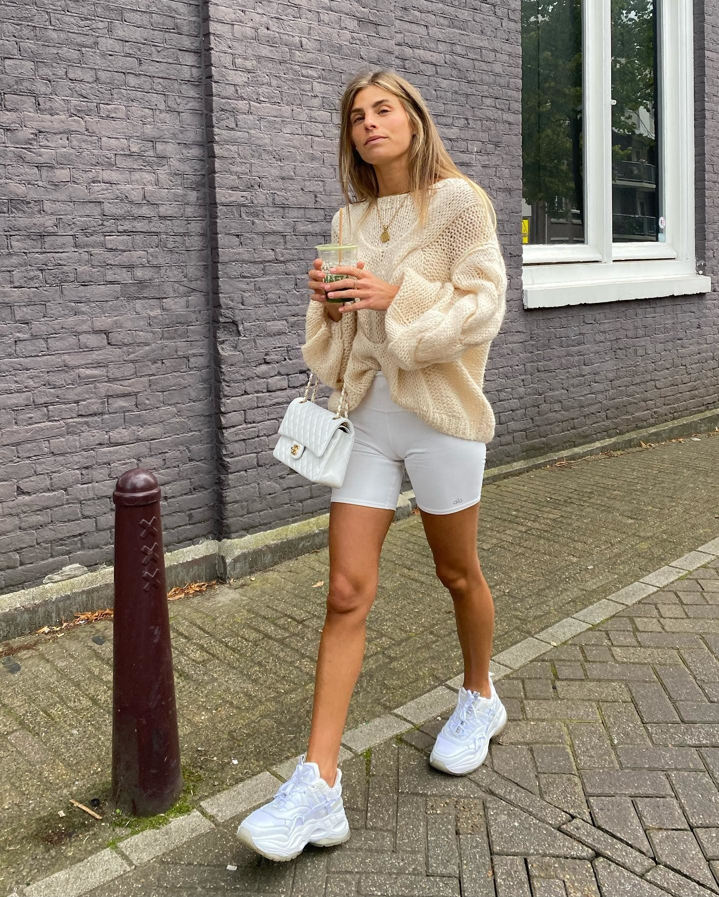 @debiflue wearing White High-Waist Biker Shorts with an oversized nude sweater, chunky white sneakers, a designer handbag, and a coffee while walking around town.