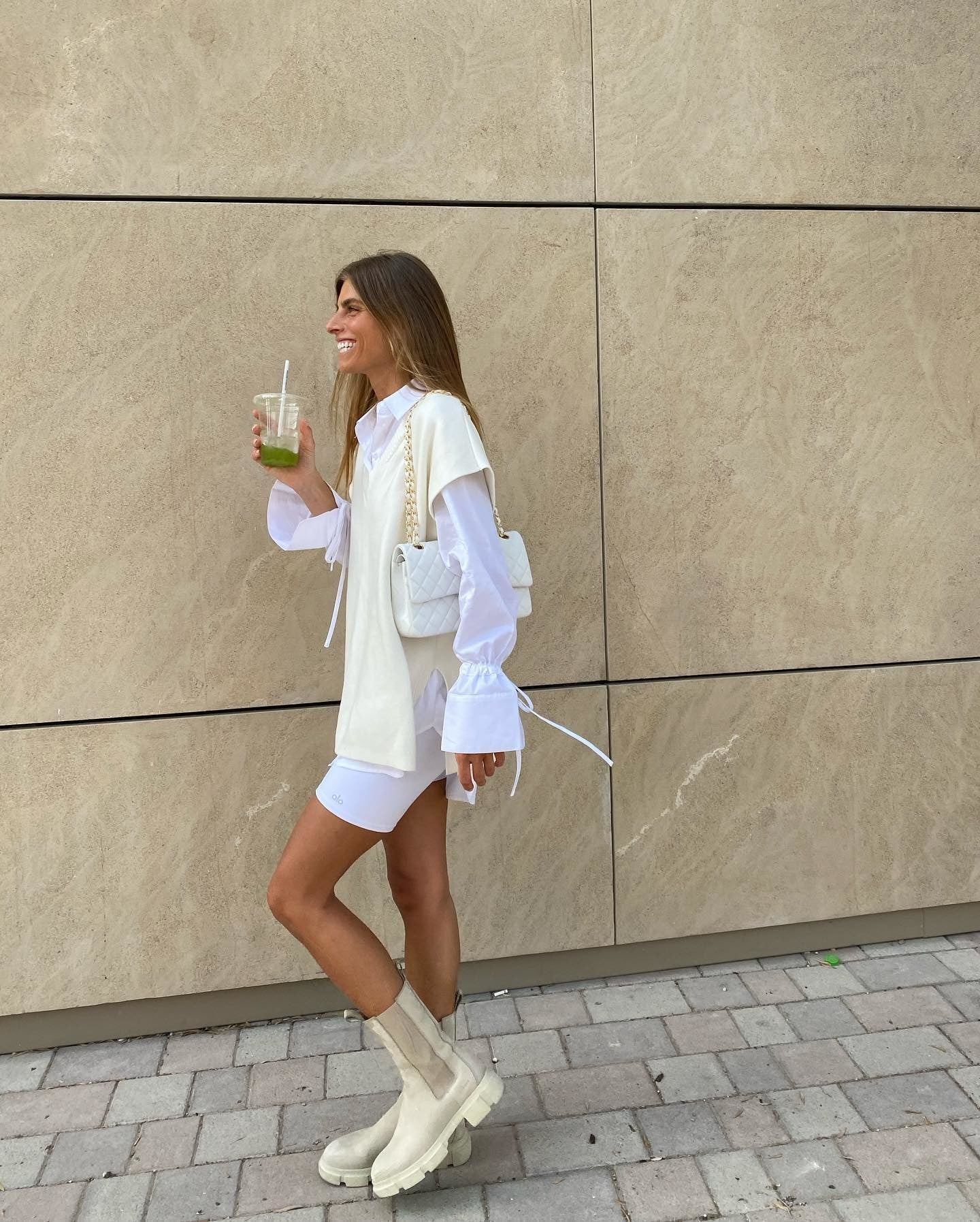@debiflue wearing white biker shorts with chunky boots, a long-sleeve dress shirt, and an oversized sweater vest for a chic biker short outfit.