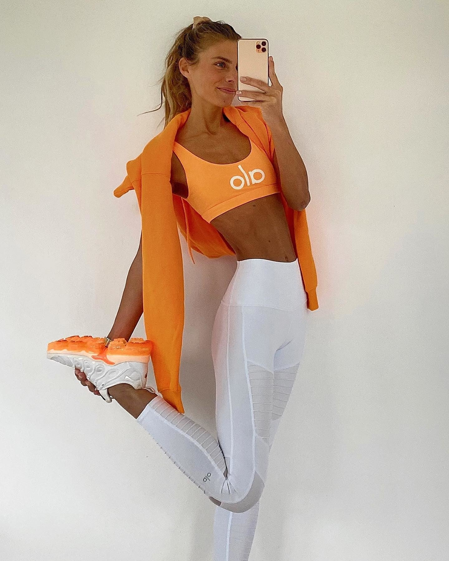 @debiflue wearing white cropped leggings that hit right above the ankle paired with a neon orange sports bra and hoodie for a perfect workout look.