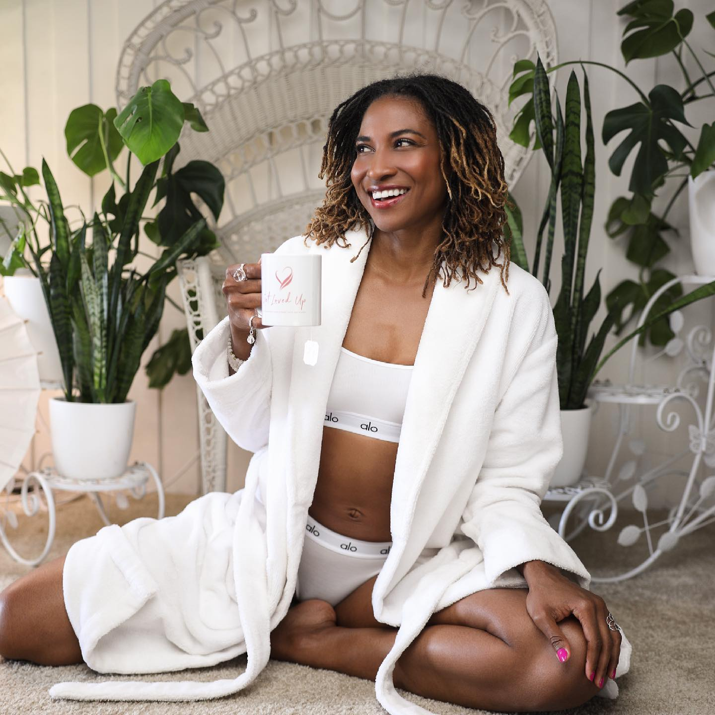 @koyawebb drinking her morning tea while wearing the Alo Icon Bra Cami and matching undies topped with a comfy white robe.
