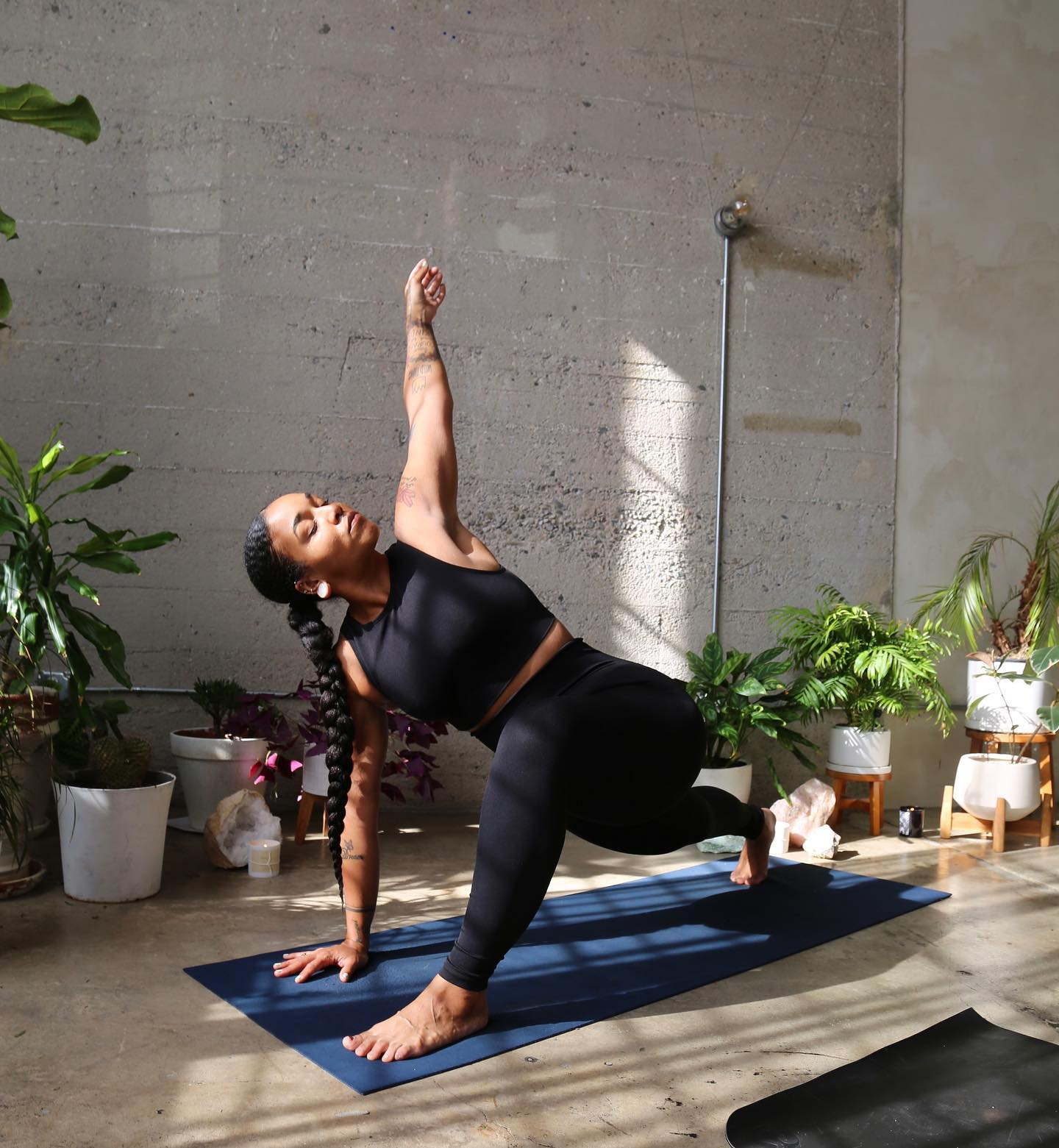 @meldouglasyoga wearing an all black workout set with high-neck cropped sports bra tank and high-waisted leggings while practicing yoga in her plant-filled studio.