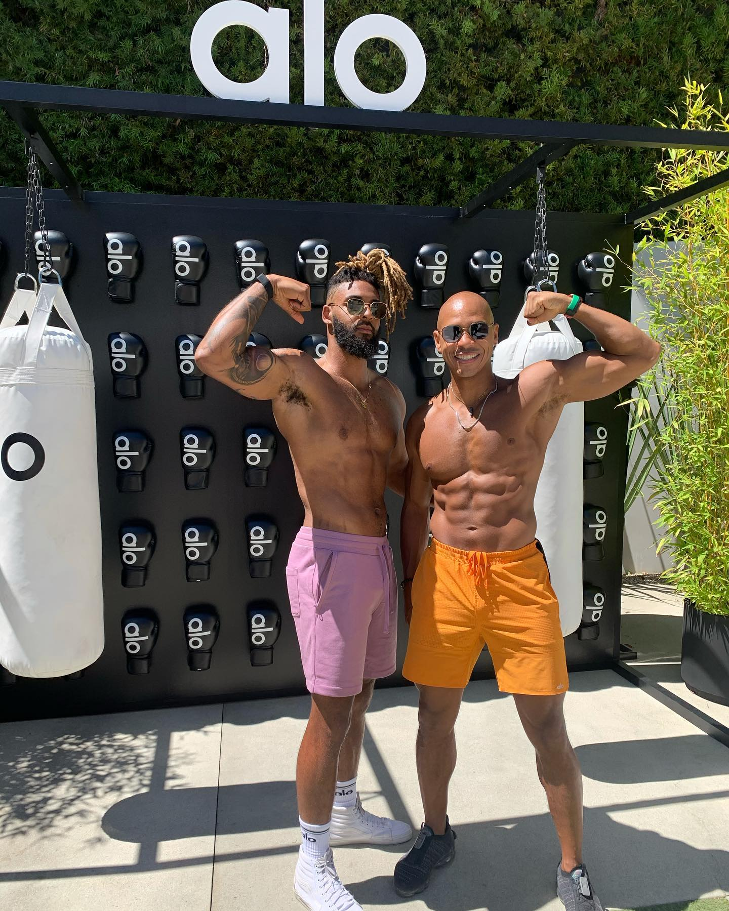 @kupahjames wearing the Traction Short in Atomic Orange and @jt_zen wearing the Chill Shorts in Purple Haze while showing off their muscles in front of the Alo Boxing Station at Alo House.