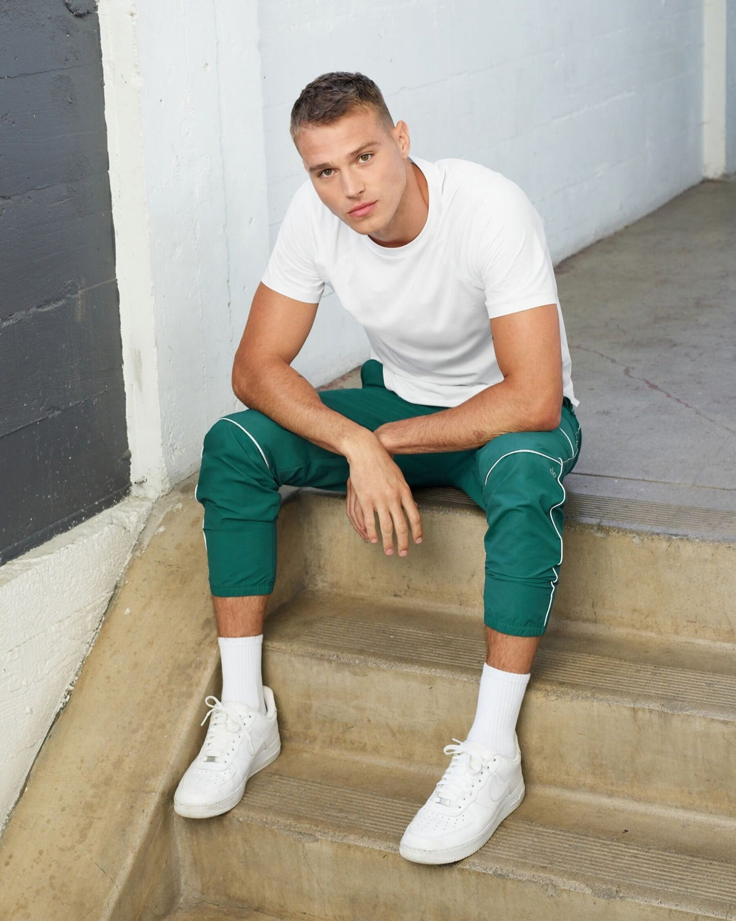 A man wearing the Torrent Track Sweatpant in Baltic green and Triumph Crew Neck Tee in White for a casual-cool street outfit