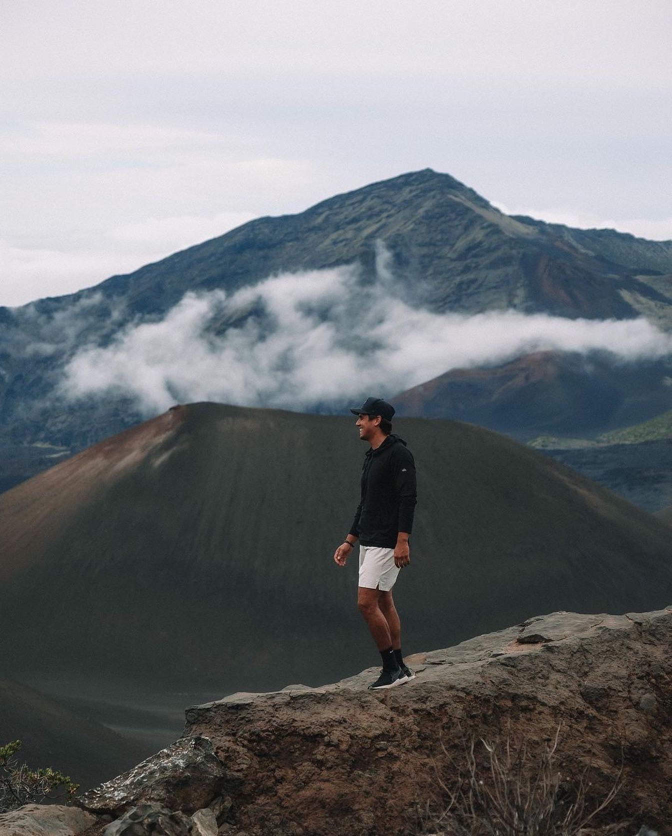@chris_avey wearing the Idol Hooded Runner while hiking through a cloudy mountain range.