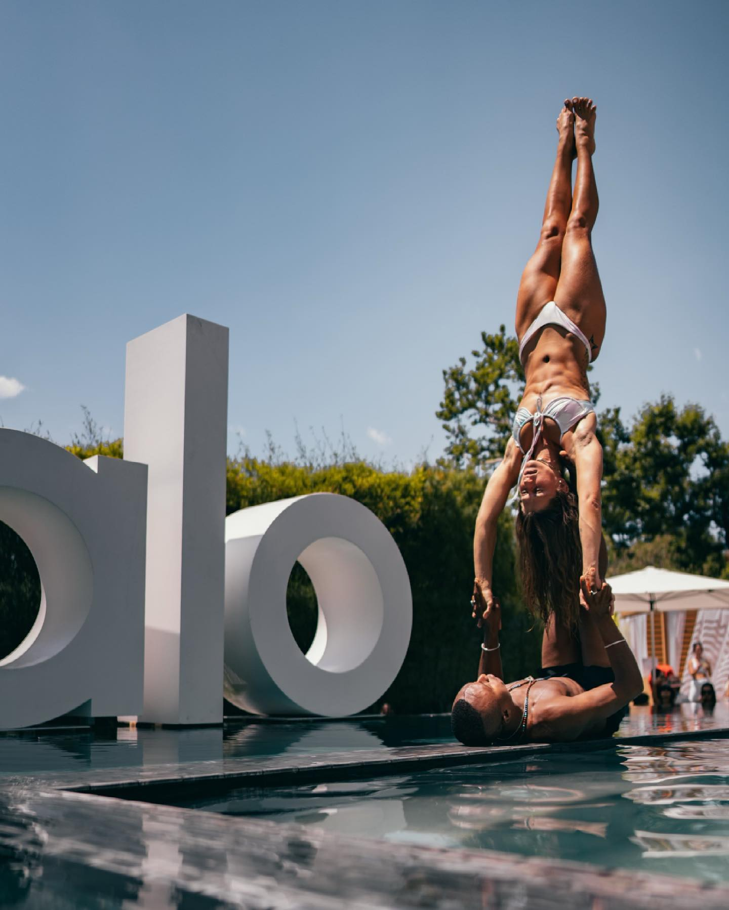 @rivkalov performing acro yoga with @andrewsealy7 at the Alo House pool.