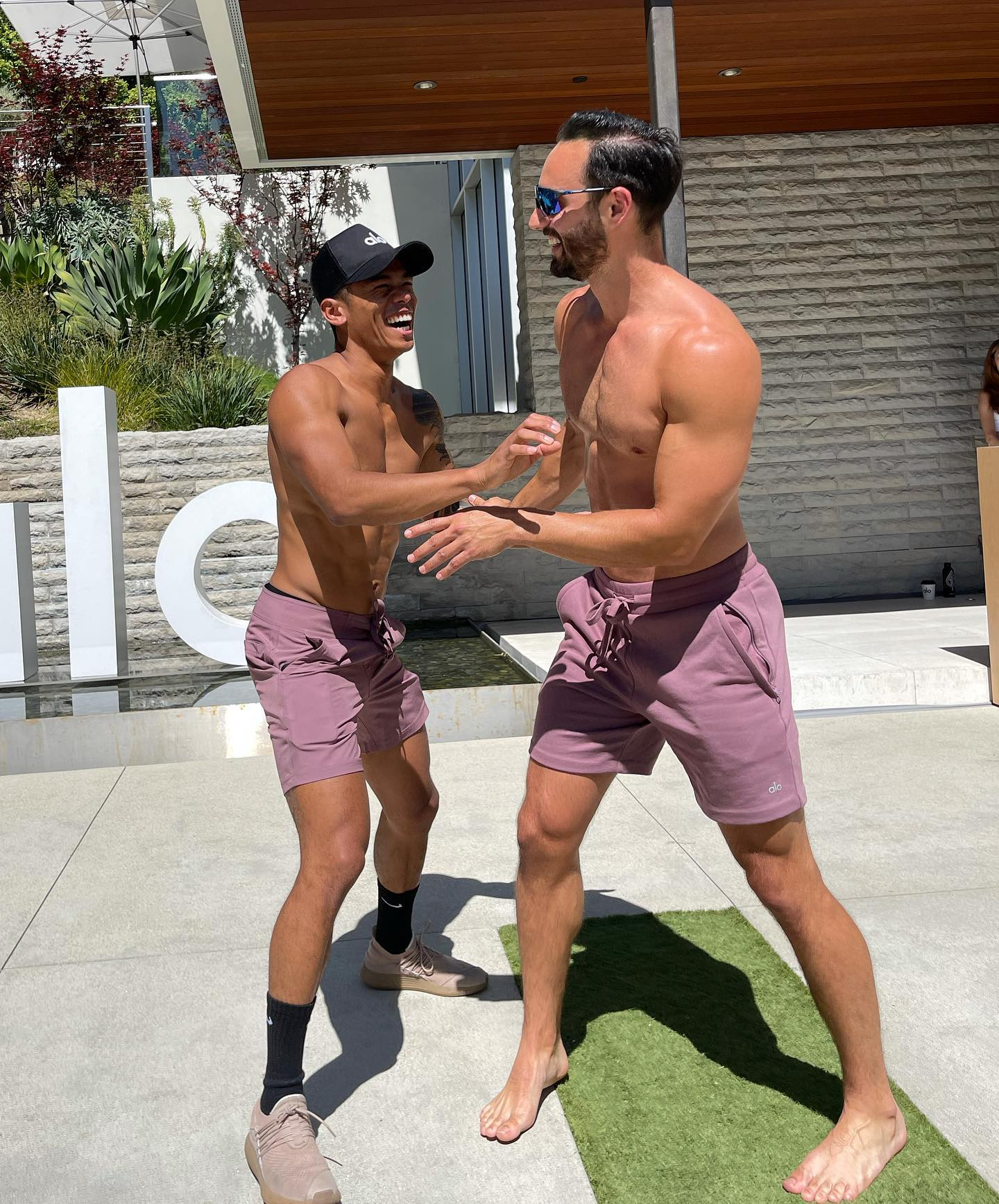 @nikkoreyes and @danielricefitness laughing together as they enter Alo House.