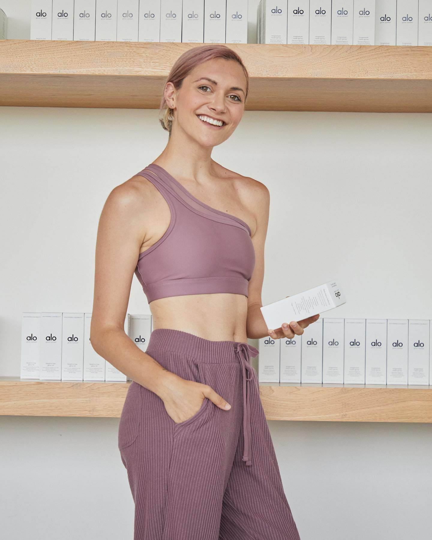 @alysonstoner wearing the Airlift Excite One-Shoulder Bra and the Muse Sweatpants both in Woodrose while checking out the Alo Glow System Products at Alo House.