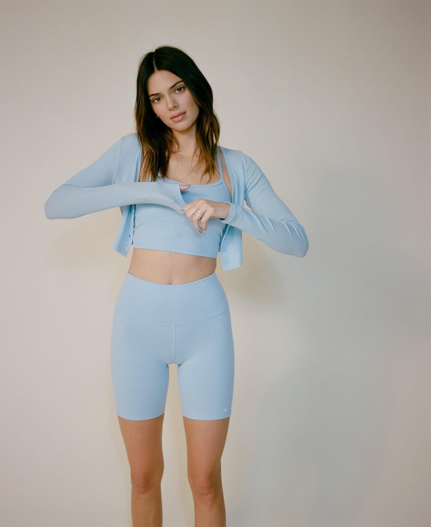 @kendalljenner wearing a head-to-toe Blue Skies outfit with High-Waist Biker Shorts, Alosoft Ribbed Calm Crop Tank, and the Ribbed Cropped Whisper Cardigan.
