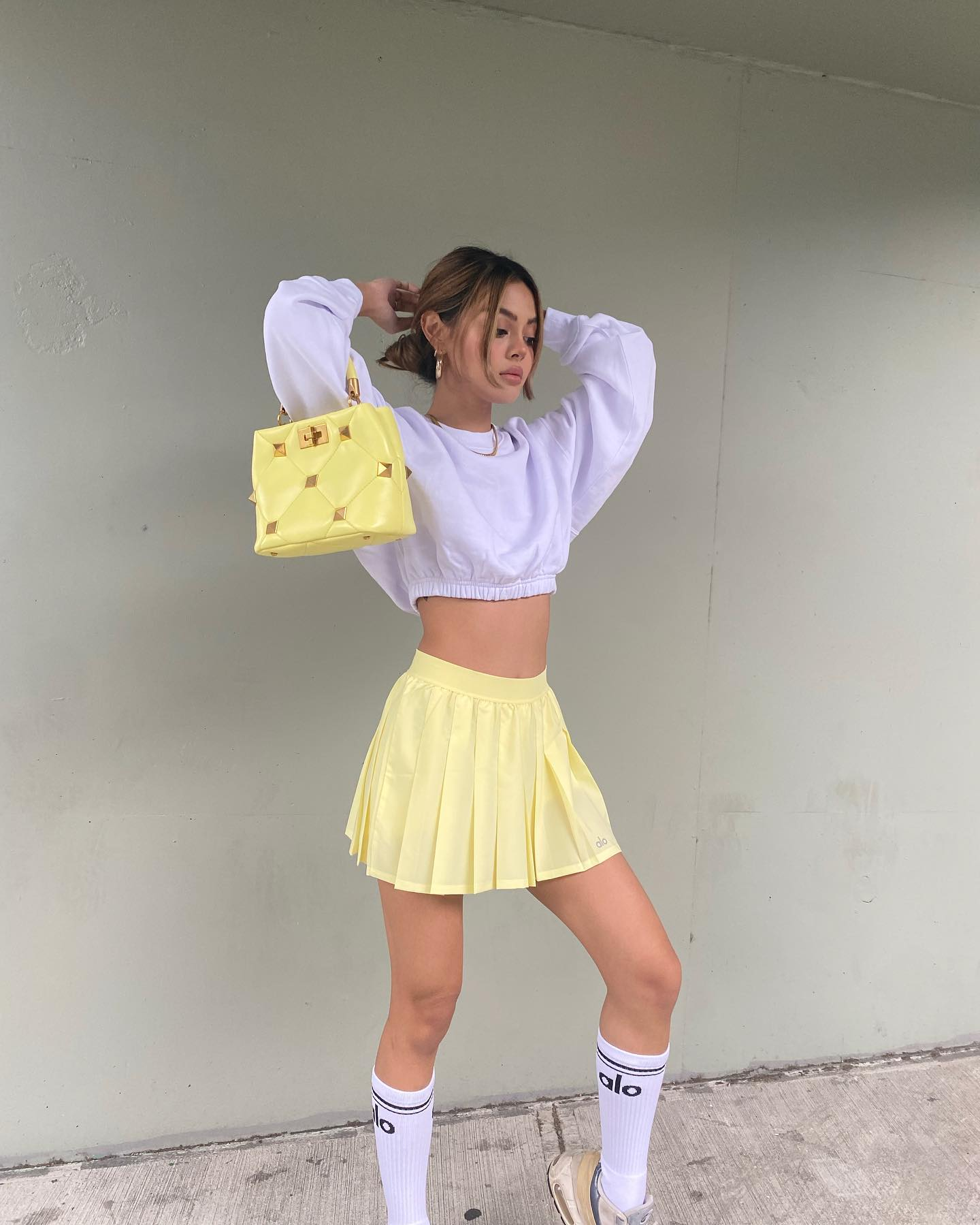 @lilymaymac wearing the Devotion Crew Neck Pullover with the Varsity Tennis Skirt in Buttercup paired with a yellow handbag for an autumn morning walk to breakfast.