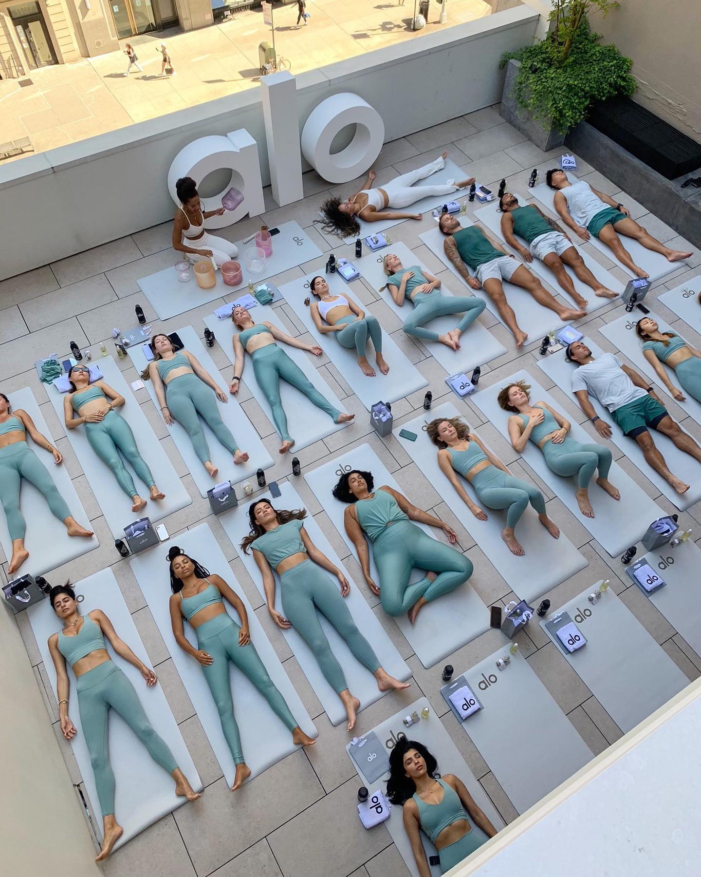 A group of yogis laying is Savasana during an Alo Moves flow at New York Fashion Week wearing Soft Seagrass on the rooftop of the Alo Flat Iron Sanctuary.