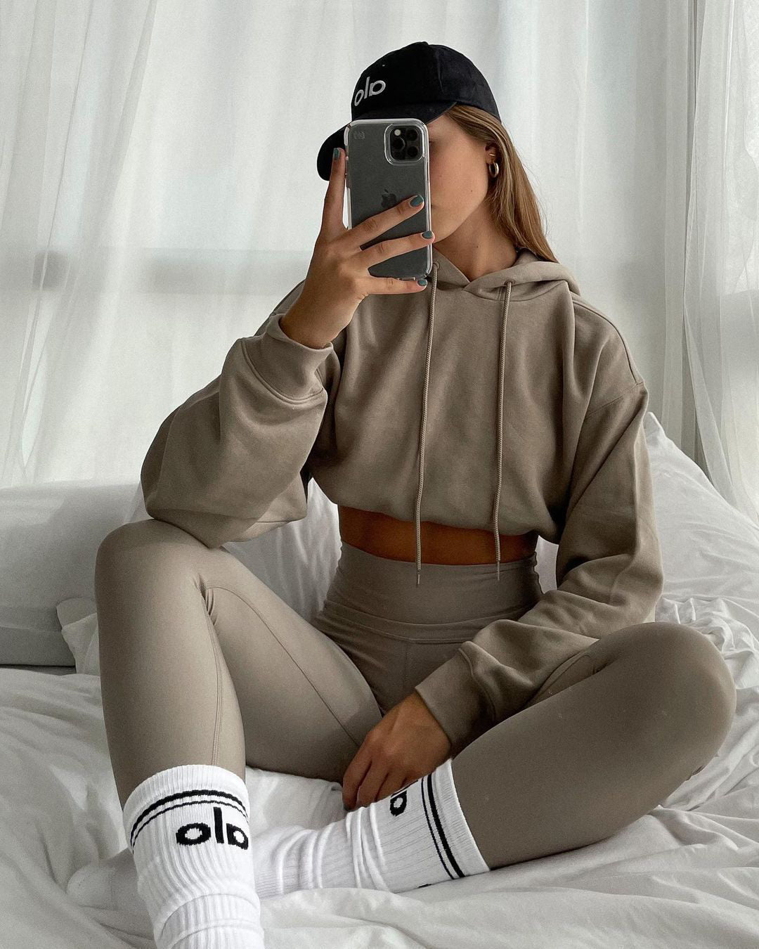 Woman wearing High-Waist Airlift Leggings with the Bae Hoodie, both in Gravel, paired with an Alo Off-Duty Cap and Woman's Throwback Socks while posing in bed for a mirror selfie.