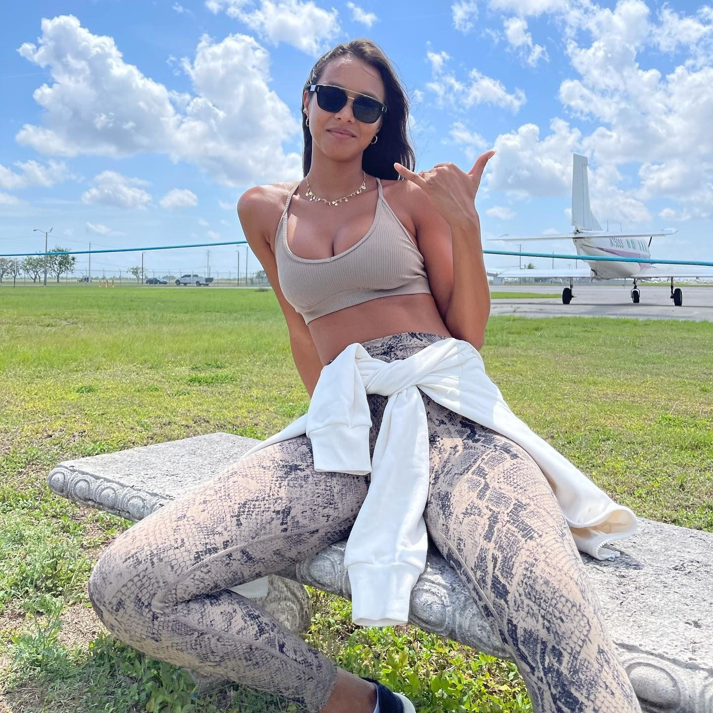 @laisribeiro wearing Gravel Snakeskin high-waisted leggings with a light brown sports bra and a white hoodie tied around her waist for a pre-skydiving picture.