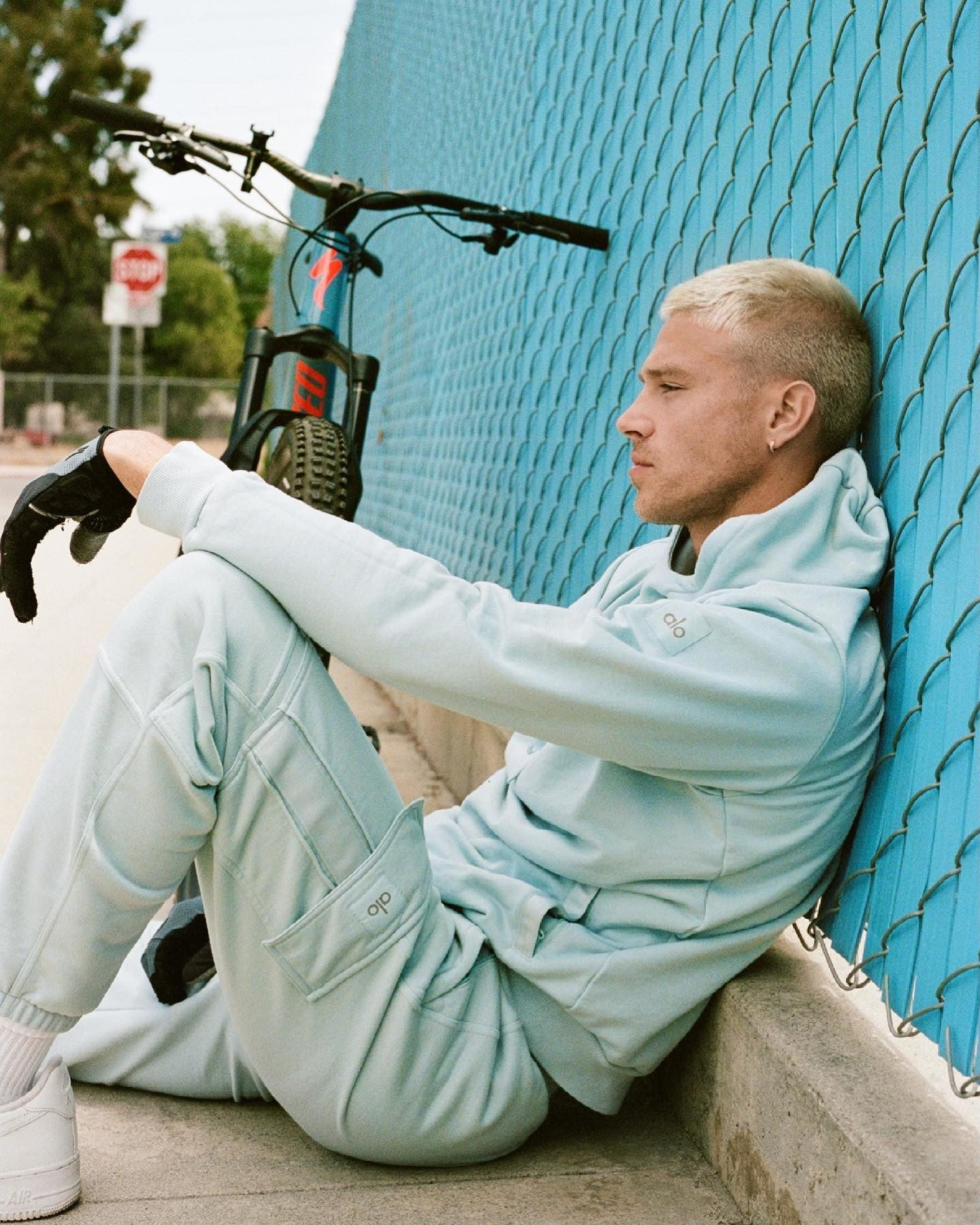 @matthew_noszka wearing the Highline Hoodie and Highline Cargo Sweatpant in Chalk Blue during a bike ride around town.