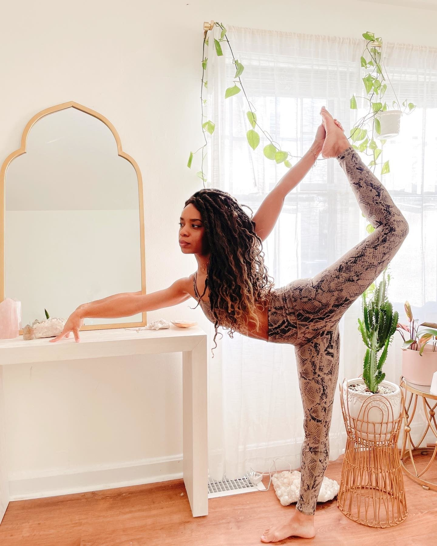 @phyllicia.bonanno wearing a matching Gravel Snakeskin workout set with high-waisted leggings and classic sports bra while stretching in her rattan-furniture- and plant-adorned living room.