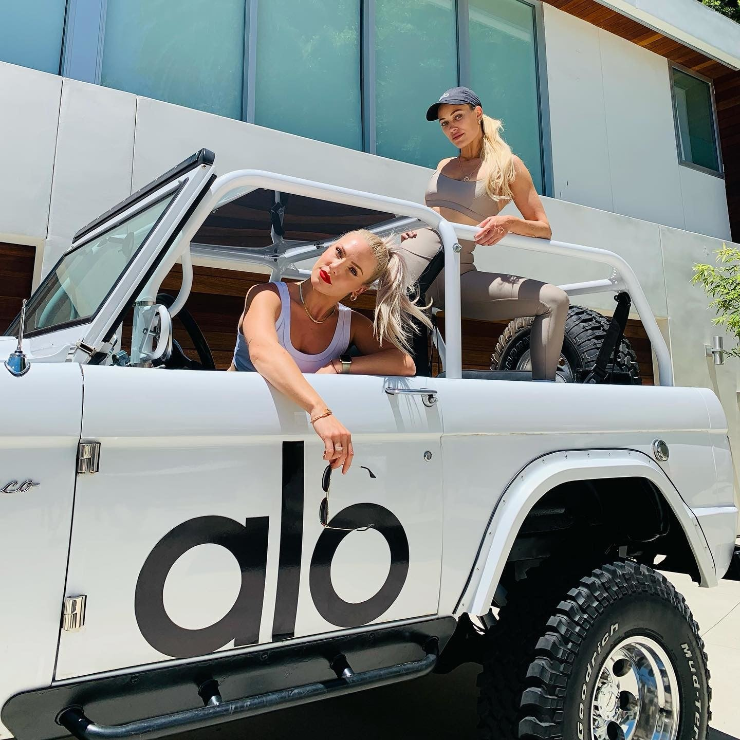 @sharnaburgess and @petamurgatroyd posing in front of the Alo Bronco at Alo House.