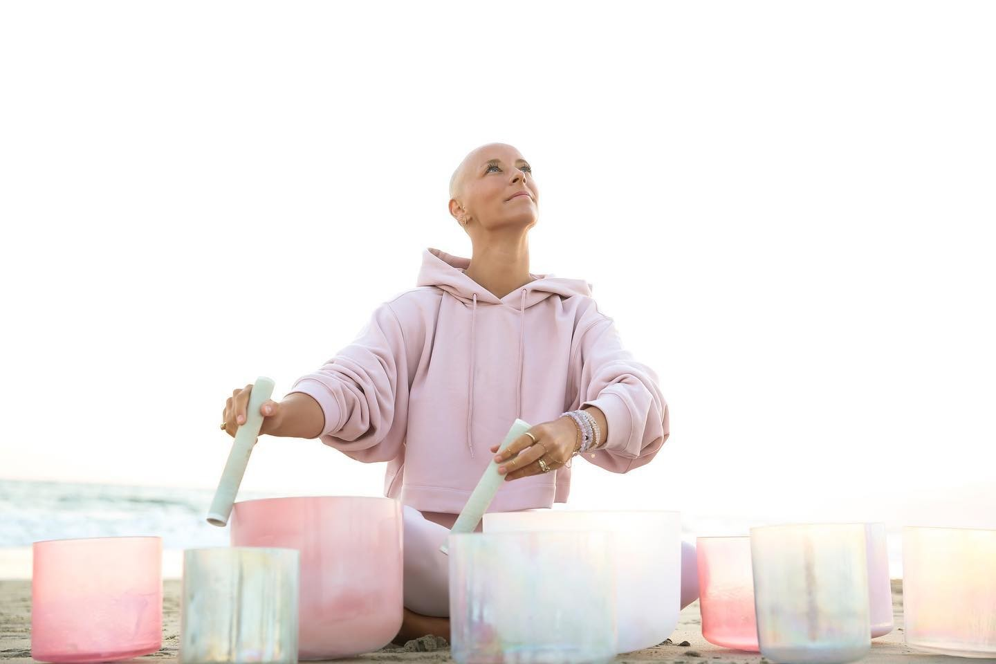@thecoppervessel performing a sound bath practice wearing a cropped pink Alo hoodie while on the beach.