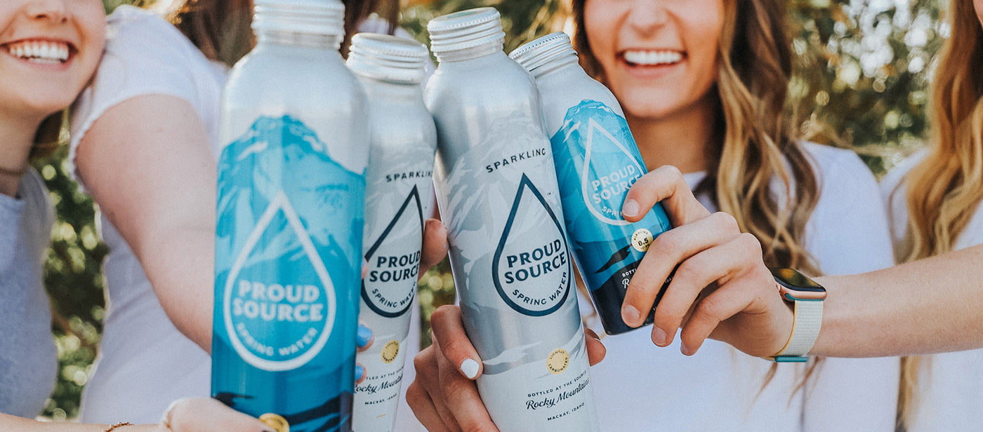 Fans of Proud Source Water holding up our aluminum bottles.