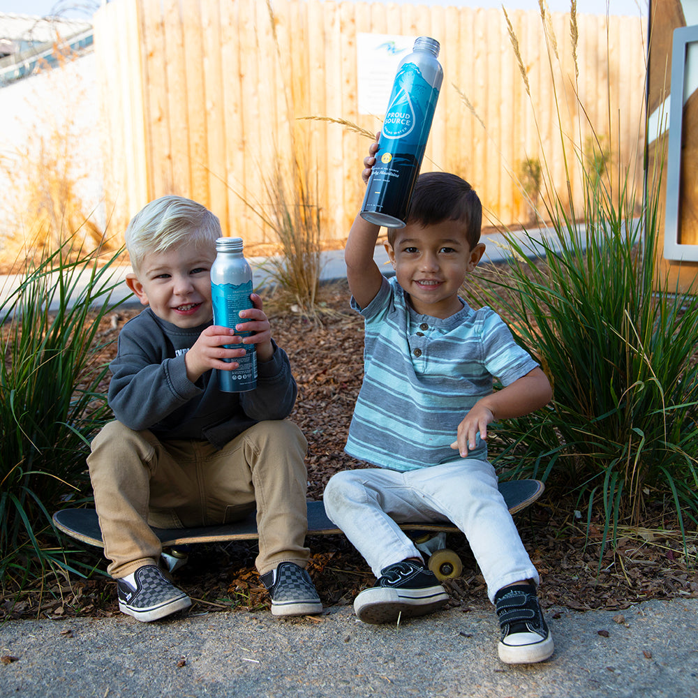 Two Cute kids hoisting up their bottles of Proud Source Water