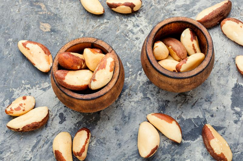 Two small bowls of raw Brazil nuts on a table