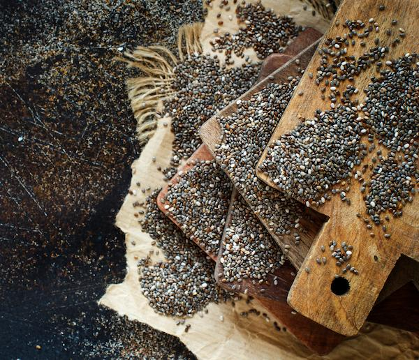 Wooden chopping boards with chia seeds spread all over them