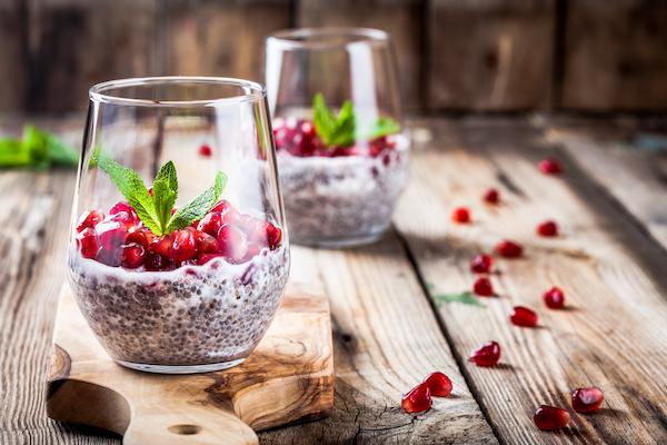 Two glass jars of chia seed pudding with berries