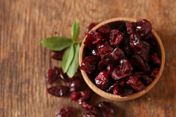 Bowl of dried cranberries on wooden background