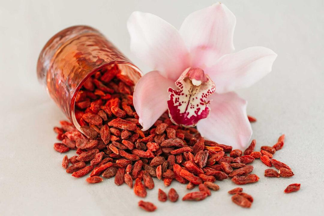 A pile of goji berries with a hibiscus flower