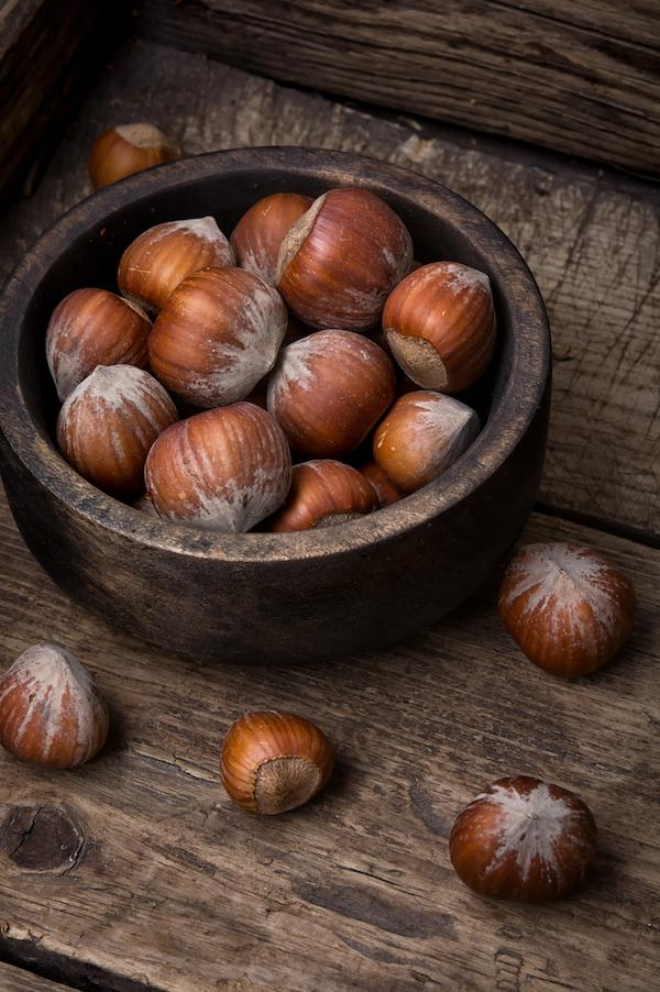 A small bowl of hazelnuts on a table