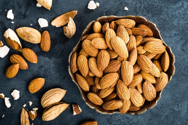 Mood boosting almond nuts in a bowl with some scattered around