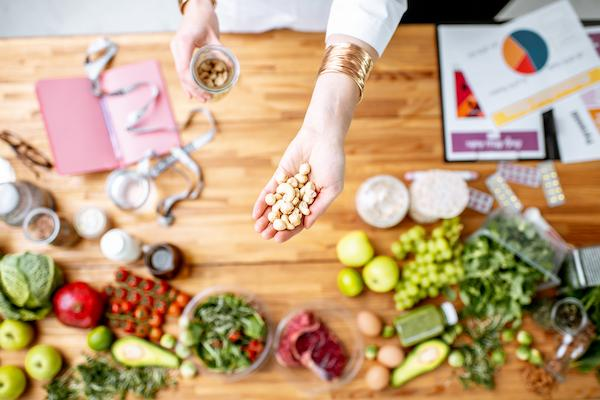 Dietitian holding mood boosting nuts above the table full of healthy food