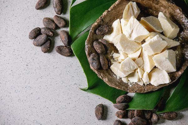 Bowl of cocoa butter surrounded by cocoa beans