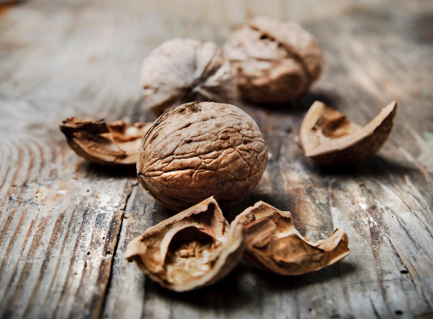Some shelled walnuts on a wood table
