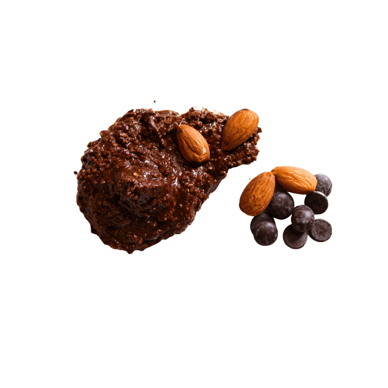 Small pile of Dark Chocolate Chips and whole Dry Roasted Almonds sitting next to a smear of Chocolate Almond Butter.