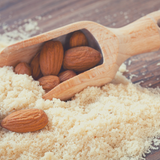 Timber spoon full of raw whole almonds sitting in a handful of Blanched Almond Meal.