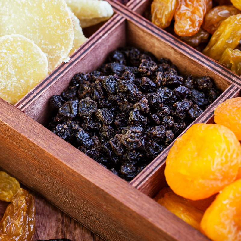 Close up of Currants in a timber dried fruit gift box, next to various dried fruit.