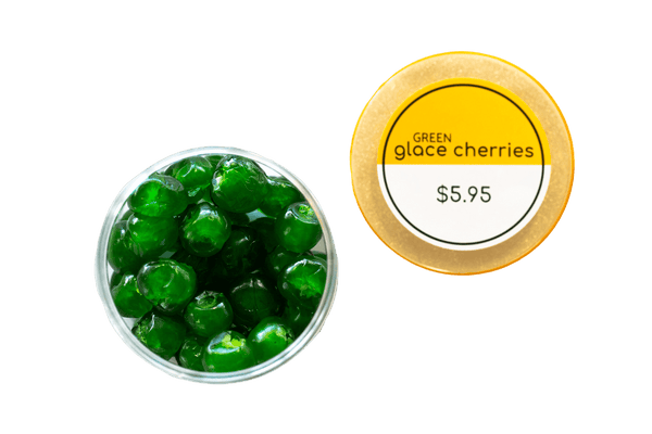 Glace Cherries Green in open Nut Market jar. Yellow lid sitting beside jar.