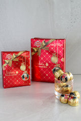Christmas Gift Boxes of Mozart Kugeln with individual Mozart Balls scattered in front.