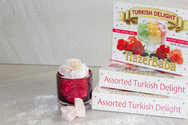 Boxes of Hazer Baba Assorted Turkish Delight sitting next to red glass jar of Turkish Delight pieces spilling over.