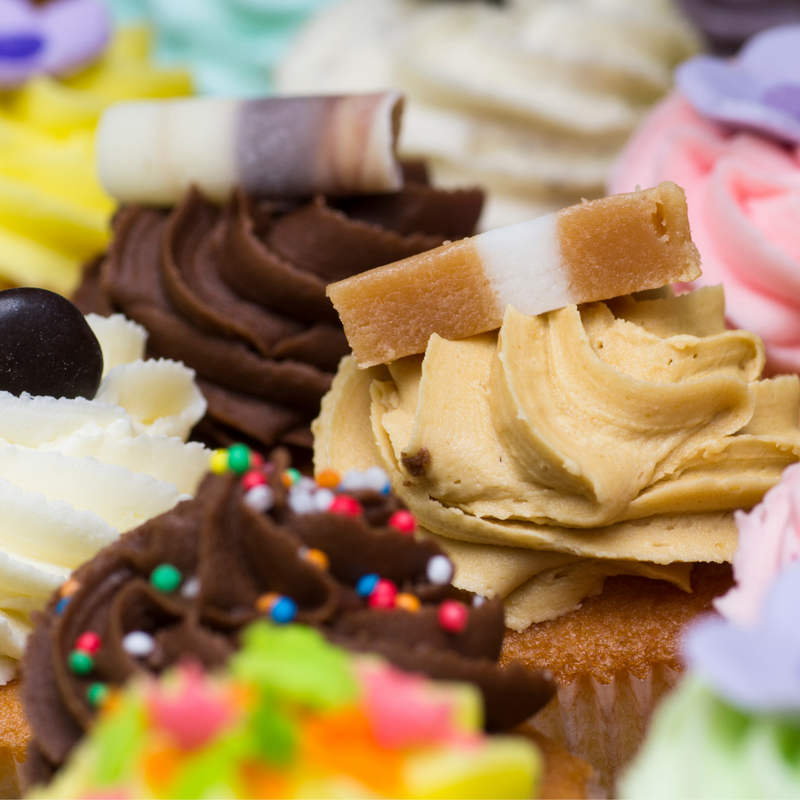 Close up of Jersey Caramel on top of cupcake, surrounded by colourful iced cupcakes.