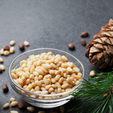 Small glass bowl of Pine Nuts on dark background. Pine Nuts scattered around the bowl and pine cone in background.