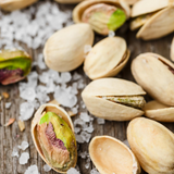 Close up of Pistachio Nuts Roasted and Salted on timber background with salt crystals.