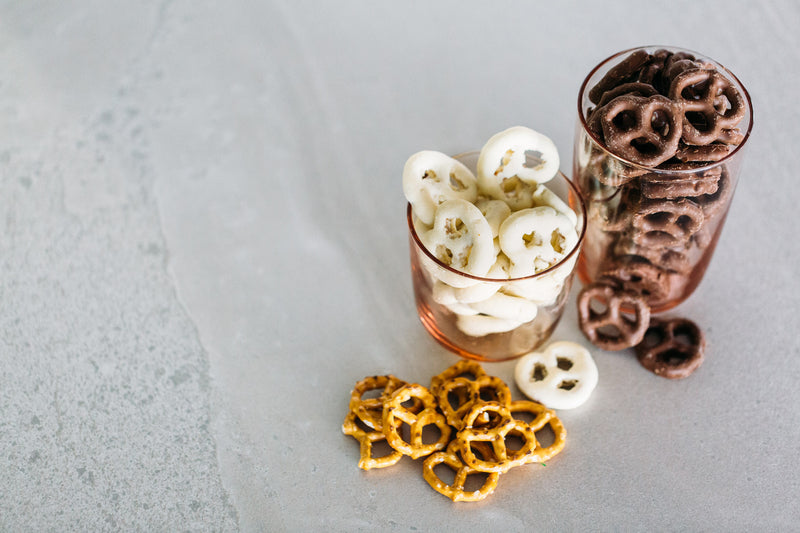 Milk Chocolate Pretzels and Yoghurt Coated Pretzels in glasses, on concrete background.