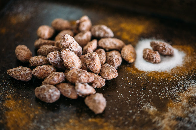 Small pile of Roasted Cinnamon Almonds on dark background. Dusted with sugar and cinnamon.